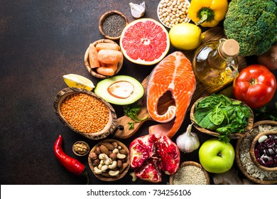 Balanced diet food background. Organic food for healthy nutrition, superfoods. Meat, fish, legumes,  nuts, seeds, greens, oil and vegetables. Top view copy space on dark stone table.