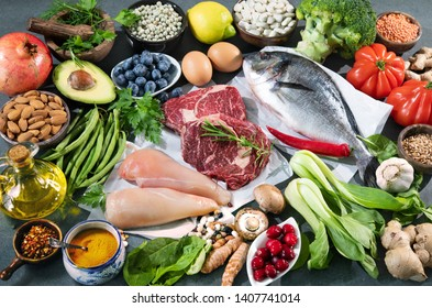 Balanced diet food background. Selection of various paleo diet products for healthy nutrition. Superfoods, meat, fish, legumes, nuts, seeds, greens and vegetables