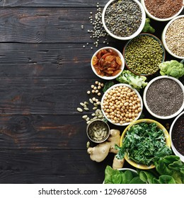Balanced diet food raw seeds, cereals, beans, superfoods and green vegetables on dark wooden table top view. Vegetarian or diet food