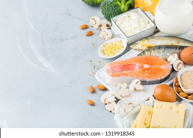 Balanced diet nutrition, healthy eating concept. Assortment of food sources rich in vitamin d and calcium, salmon, dairy products, sardines, broccoli on a kitchen table. Copy space background