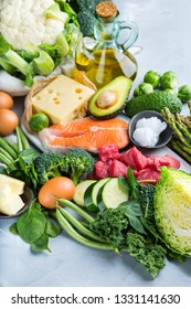 Balanced diet nutrition keto concept. Assortment of healthy ketogenic low carb food ingredients for cooking on a kitchen table. Green vegetables, meat, salmon, cheese, eggs