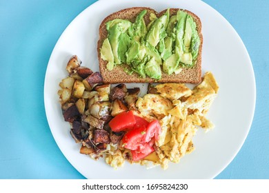 Balanced healthy vegetarian breakfast avocado toast, scrambled eggs, potatoes and tomato.