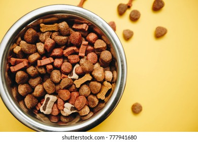 Balanced meal for a pet. A bowl of dry dog food on a bright one-color yellow background, top view. Pet care and veterinary concept. Spase for your text or image.