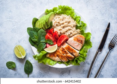 Balanced nutrition. Fresh salad from quinoa, chicken breast, avocado, spinach, lettuce and tomatoes. Healthy food. Portion plate. Top view.