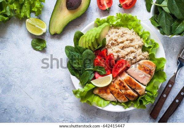 Balanced nutrition. Fresh salad from quinoa, chicken breast, avocado, spinach, lettuce and tomatoes. Healthy food. Portion plate. Top view copy space..