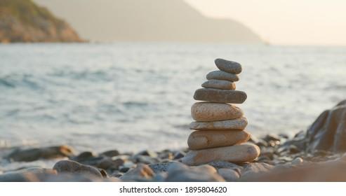 Balanced pebble pyramid on the beach at sunset