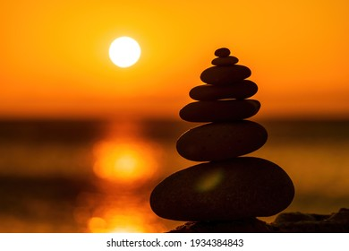 Balanced pebble pyramid silhouette on the beach. Abstract warm sunset bokeh with Sea on the background. Zen stones on the sea beach, meditation, spa, harmony, calmness, balance concept Selective focus