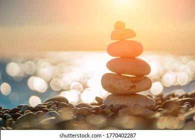 Balanced Pebbles Pyramid on the Beach on Sunny Day and Clear Sky at Sunset. Blue Sea on Background Selective focus, zen stones on sea beach, meditation, spa, harmony, calm, balance concept