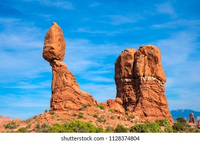 Balanced rock in arches national park with blue sky and white clouds