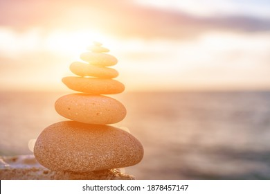 Balanced rock pyramid on the pebble beach on sunset. Selective focus Abstract bokeh from Sea foam on the background. Zen stones on the sea beach, meditation, spa, harmony, calmness, balance concept