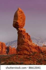 Balanced Rock at twilight in front of the snow covered La Sal Mountains in Arches National Park near Moab, Utah
