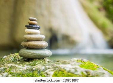 Balanced Rock Zen Stack in front of waterfall.