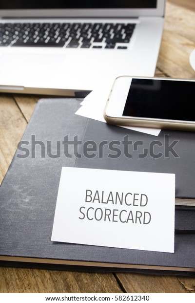 Balanced Scorecard text on business card at desktop in office with laptop, tablet computer and phone.