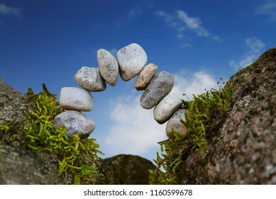 balanced stone arch of pebbles as zen symbol for a bridge or a gate, blue sky, selected focus