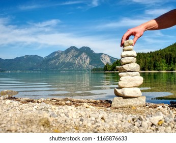Balanced stone pyramide on shore of blue water of mountain lake. Blue mountains in water level mirror.