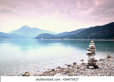 Balanced stone pyramide on shore of blue water of mountain lake. Blue mountains in water level mirror