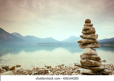 Balanced stone pyramide on shore of blue water of mountain lake. Blue mountains in water level mirror.  Poor lighting conditions.