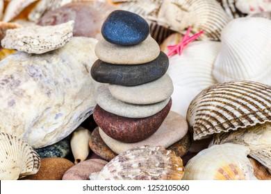 Balanced stones between variety of seashells