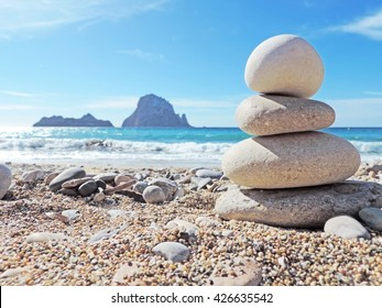Balanced stones on the beach Cala d'Hort, Ibiza Island. View to the magic rock es Vedra in the background