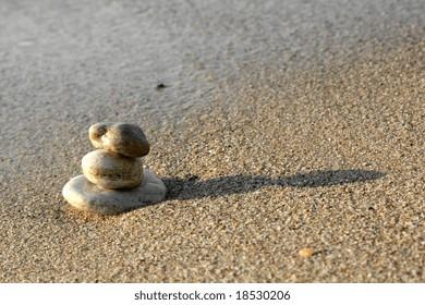 Balanced stones on sand at seashore