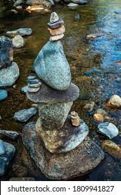 balanced stones Zen rock art in tall stack in water of mountain stream