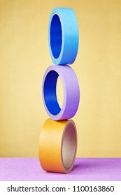 Balanced tower of three rolls adhesive tape different colors and various uses standing on its narrow side, on yellow background.
