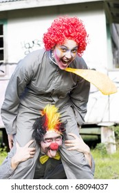 A Balancing Act Sees A Clown Riding On Another Clowns Back In A Playful Display Of Clowning Around