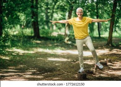 Balancing exercise outdoors. Mature woman standing on one leg, exercising balance