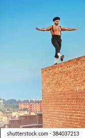 Balancing high. Shot of a shirtless retro male builder walking balancing on a brick wall