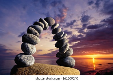 Balancing of pebbles on the boulder in the evening