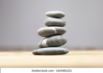 balancing pebbles on wooden table, space for text. Zen concept