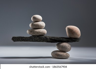 Balancing pyramid of sea pebbles on a gray background, the concept of harmony and balance, heavy and light. Stones in the form of scales with balancing stones.