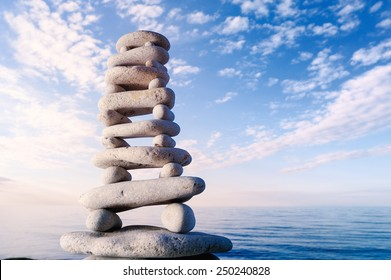 Balancing of stones each other on sky background at the sea