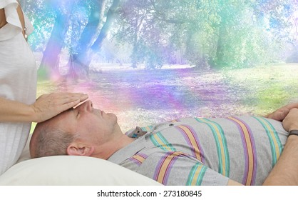 Balancing Third Eye Chakra - Healing practitioner sensing energy of male client lying supine on couch with a colorful fantasy rainbow bokeh background