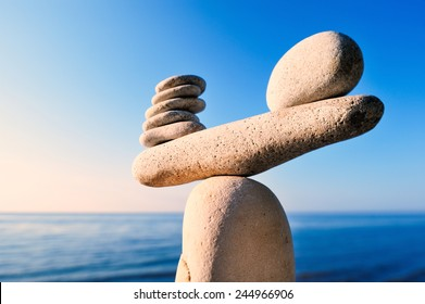 Balancing of white pebbles on the top of stone
