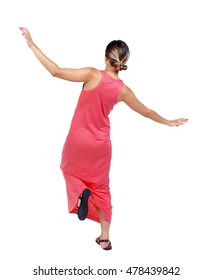 Balancing young woman. or dodge falling woman. slender woman in a long red dress balancing on his leg.