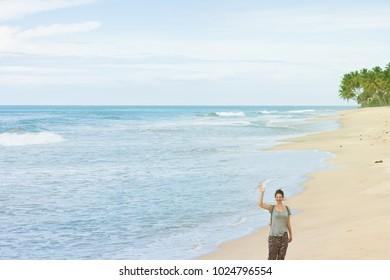 Balapitiya Beach, Sri Lanka - A young woman waving her hand at the beach of Balapitiya