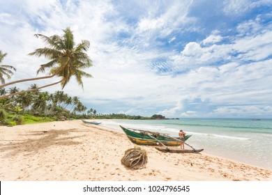 Balapitiya, Sri Lanka, Asia - A woman preparing for a canoe tour at the beach of Balapitiya