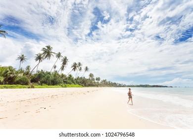 Balapitiya, Sri Lanka, Asia - A young woman going for a walk at the beach of Balapitiya