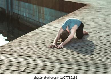 Balasana es una postura de yoga para evitar el dolor de espalda, un joven la practica.