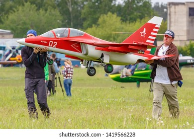 Balashikha, Moscow region, Russia - May 25, 2019: Team members of Aviation Sports Club RusJet carry a RC model of Russian jet combat-training aircraft Yak-130. Festival Sky Theory and Practice 2019