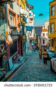 Balat, Istanbul, Turkey - February 23, 2021 - vertical view of tourists in a famous street in Balat with traditional houses and cars