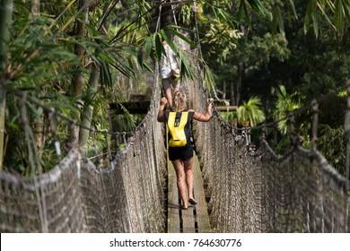 Balata Garden, Martinique : woman crossing a hanging bridge