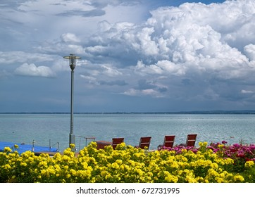 Balaton lake and puffy clouds above it at rainy summer day, with lot of flowers and deck chairs at foreground, as viewed from promenade of Balatonfured town, famous resort area of Hungary.
