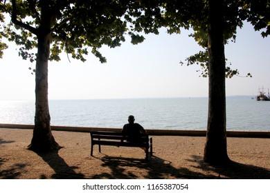 Balatonfured, Hungary 08.17.2018 esplanade at shore Lake with man siluette