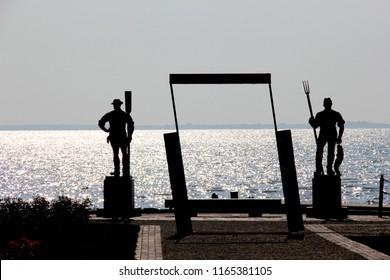 Balatonfured, Hungary - 08.17.2018 The Fisherman and the Ferryman statues at the port of Balatonfured, siluettes