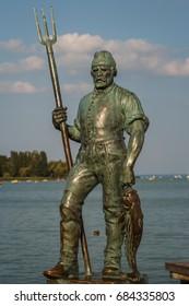 BALATONFURED / HUNGARY - AUGUST 2014: Figure of fishman on the shore of Balaton lake in Balatonfured, Hungary