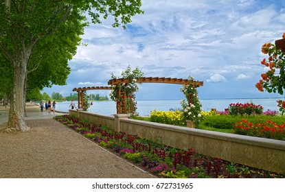 BALATONFURED, HUNGARY - JUNE 02, 2016: Promenade of Balatonfured town at coast of Balaton lake, which is famous resort area of Hungary. Lot of flowers at foreground.