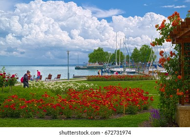 BALATONFURED, HUNGARY - JUNE 02, 2016: Promenade of Balatonfured town at coast of Balaton lake, which is famous resort area of Hungary. Lot of flowers at foreground and puffy clouds on the sky.