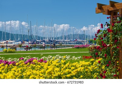 BALATONFURED, HUNGARY - JUNE 02, 2016: Promenade of Balatonfured town at coast of Balaton lake, which is famous resort area of Hungary. Flowers at foreground and lot of yachts in the middle.